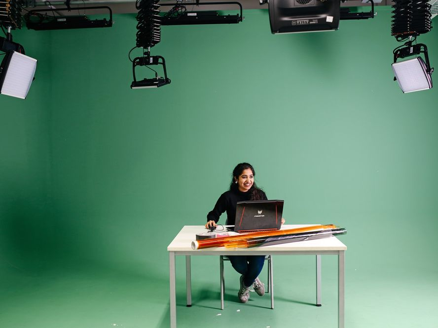 student in the green screen studio