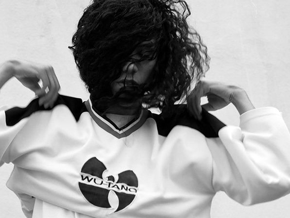 A girl putting on a jumper with 'Wu-Tang- logo