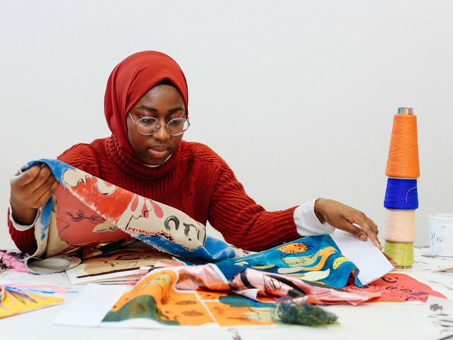 Black female student sitting at workbench looking at various brightly coloured fabrics