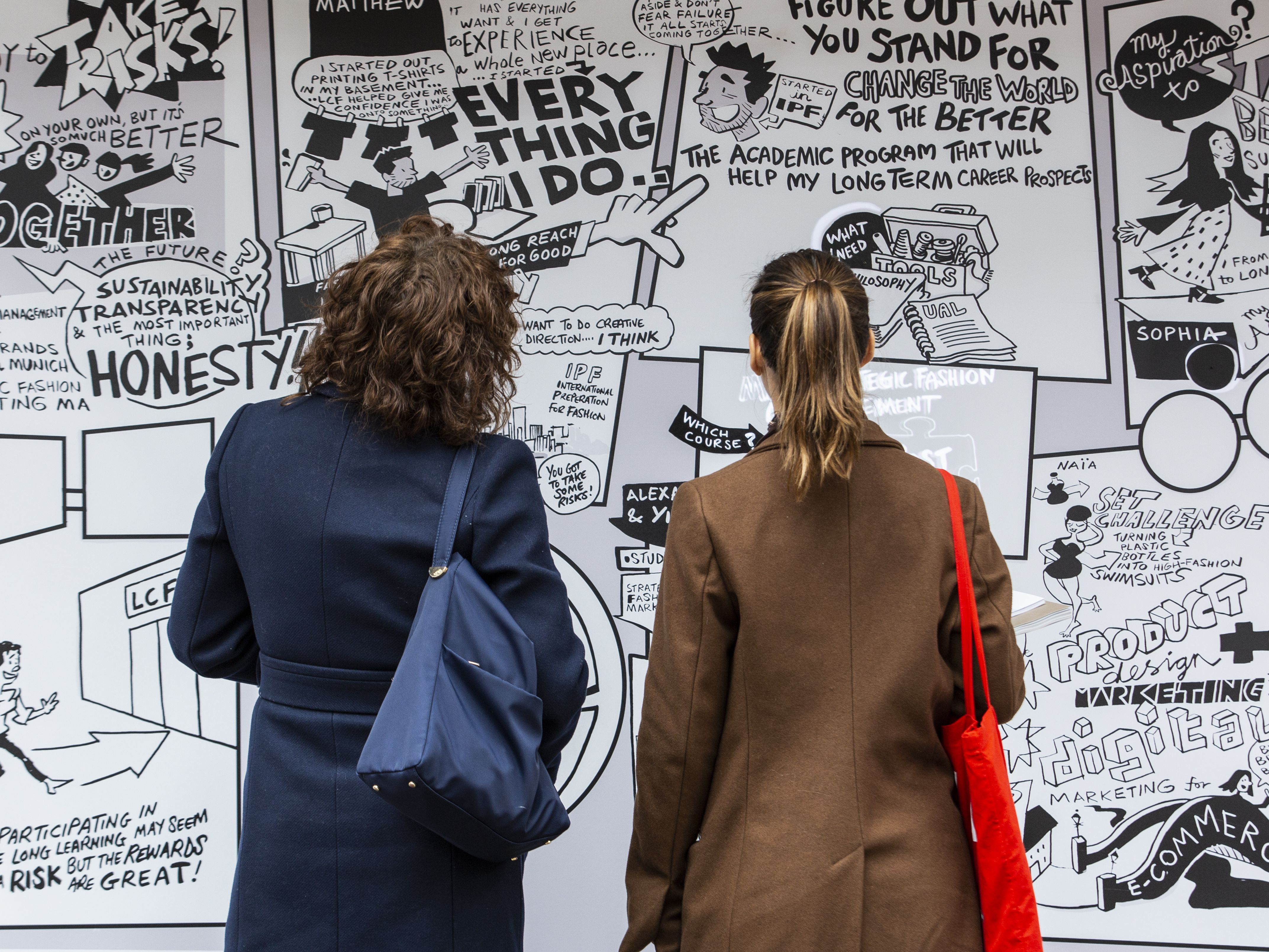 Two people standing up in front of a poster during an exhibition