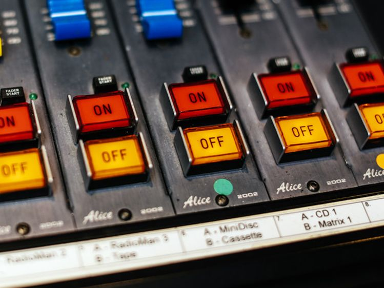 red 'on' and yellow 'off' buttons on a sound mixing desk