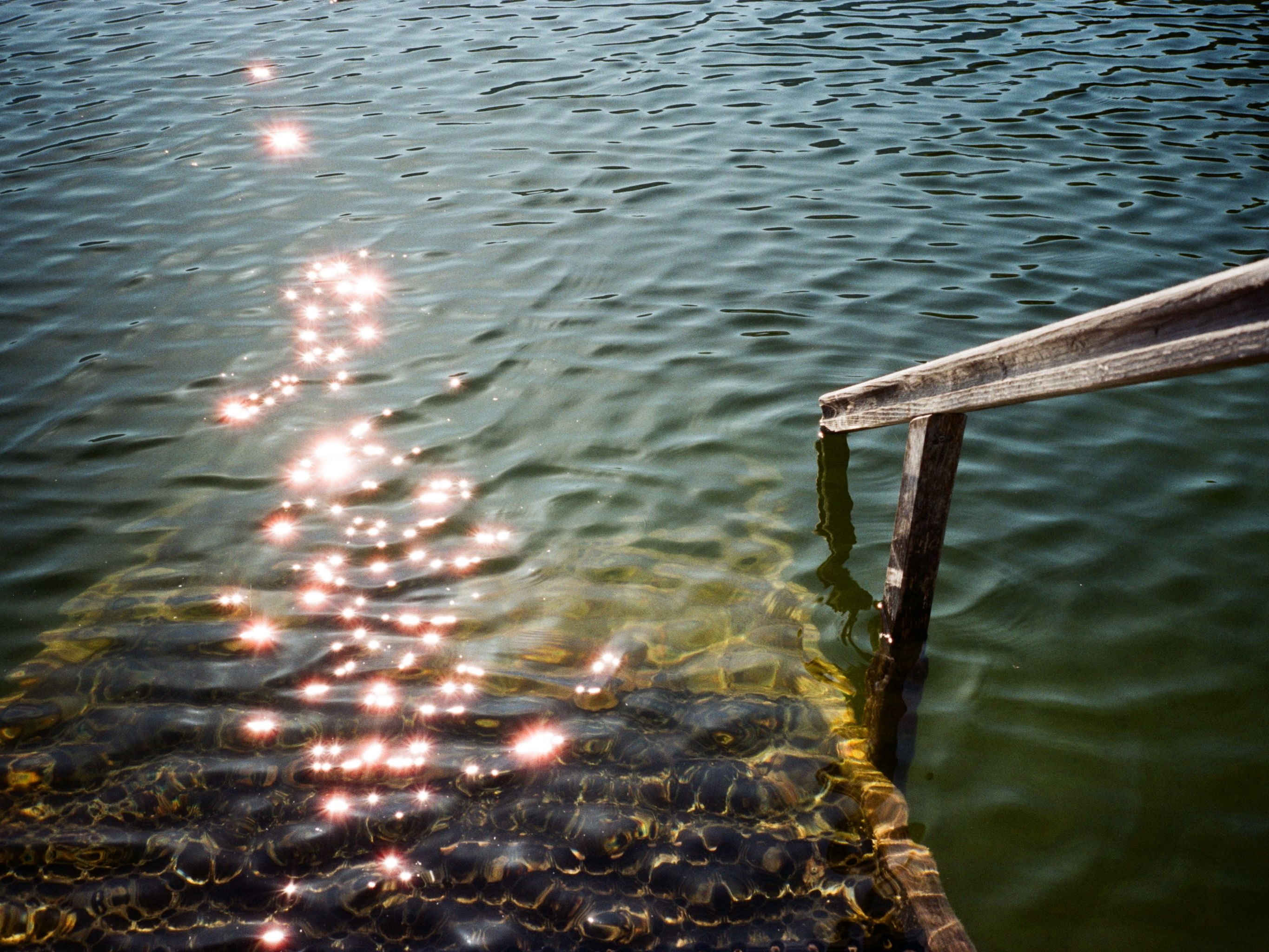Photograph of steps down into the water in a lake taken on a sunny day with the sun glistening on the water by Pippa Healy - MA Fine Art: Printmaking