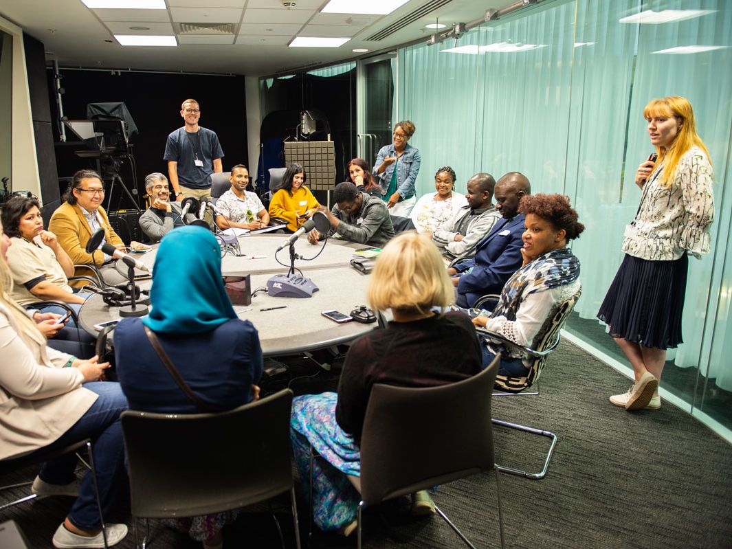 Participants of the Refugee Journalism Project sit in the Guardian Podcast studio with Guardian colleagues.