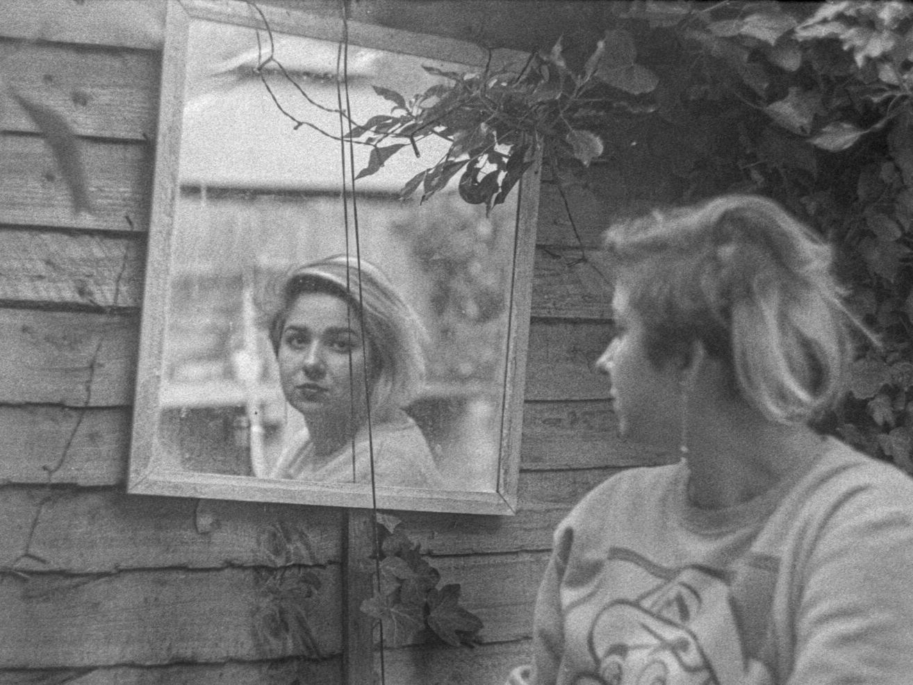 A woman looks at a mirror over her shoulder.