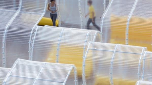 A photograph of modular transparent covered structures arranged into the shape of a wave. Two people walk through them and yellow objects can be seen amongst the structures.