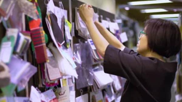 A woman looking at materials hung on a wall