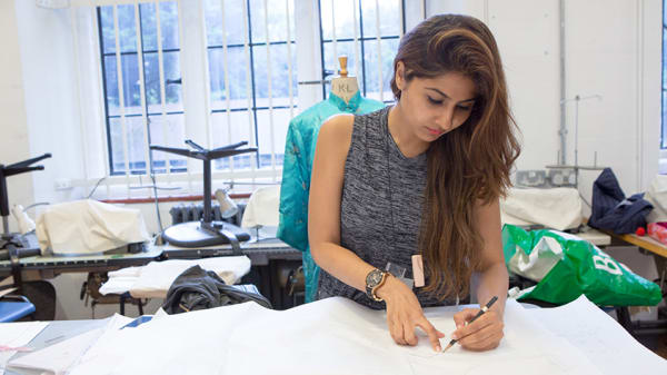 A woman cutting a clothing pattern
