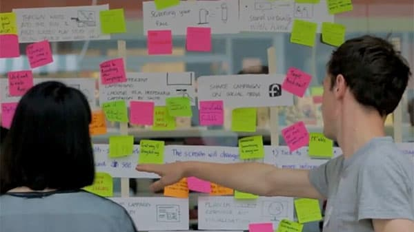 Service design workshop with two people using post-it notes