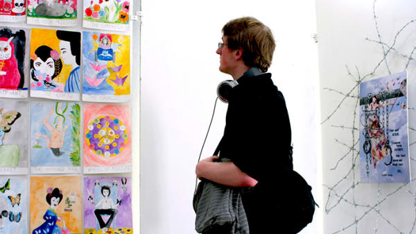 Photo of a man standing looking at brightly coloured pieces of art on a white wall