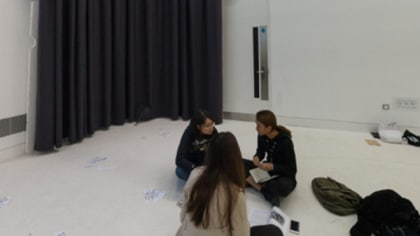 Students working in a white room with a large stage curtain hanging on the back wall