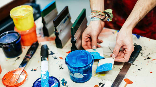 Hands using paint pots and brushes