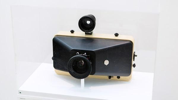 A vintage camera enclosed in a transparent box atop a plinth.
