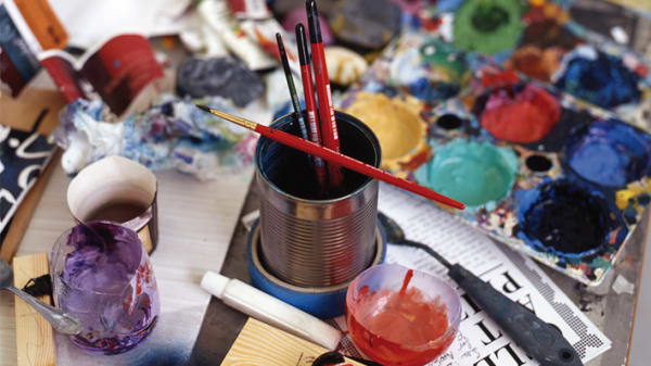 Photo of tins with paint brushes in a paint palettes