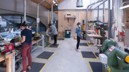 People using tools and machinery inside a large workshop at Central Saint Martins