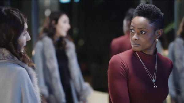 An actor wearing a red polo neck and an actor wearing a grey coat looking at one another