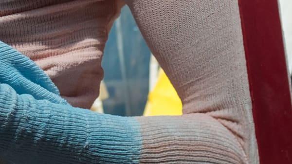 A closeup of a hand holding garments