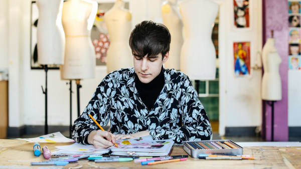 Male student sitting at desk drawing in sketchbooks, with mannequins behind him