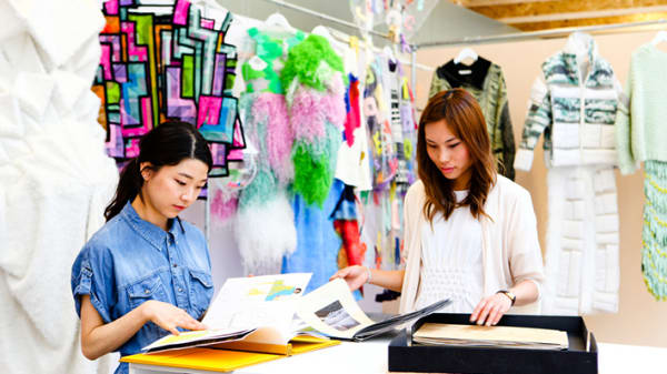 Photo of two female students looking through books on a table with clothes hanging in the background