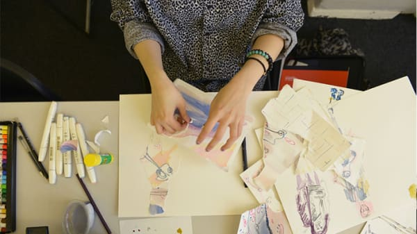 Photo taken from above of a pair of hands working with pieces of paper with drawings on them