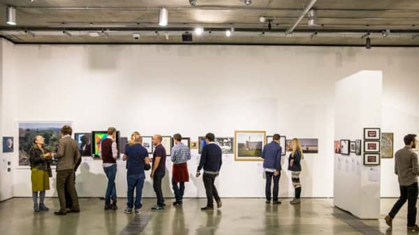 Photo of a group of people in the distance looking at art on a white wall
