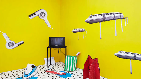 Yellow walls with the television on a table and objects in the air