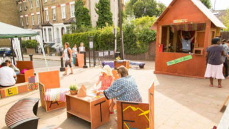 An outdoor area with a play shed and seating
