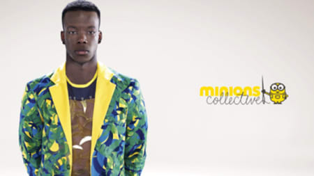 A man wearing a brightly coloured green and yellow jacket stood next to the Minions logo