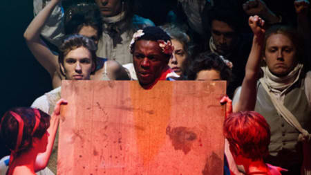 A group of actors on stage in a mob formation, the lighting over them is red.