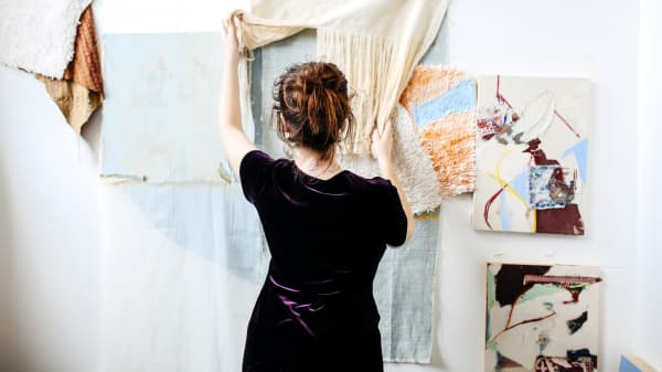 Woman hanging pieces of art and material on a white wall