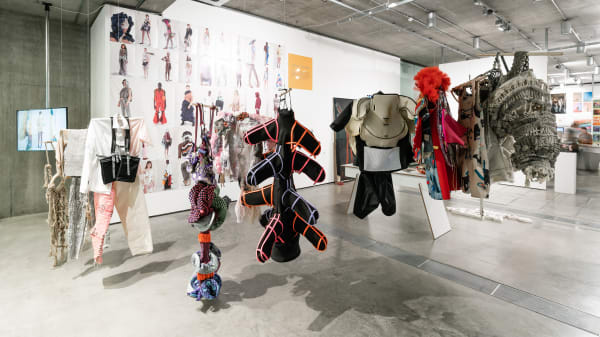 Fashion and textiles work hanging from the ceiling of a gallery