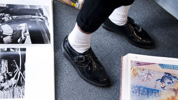 Photo of someone's feet wearing black shiny shoes with white socks standing among books on the floor