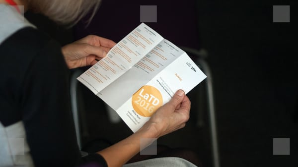 Someone holding a programme for the event