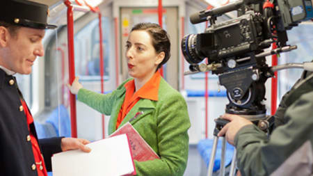 A woman being filmed on a tube carriage