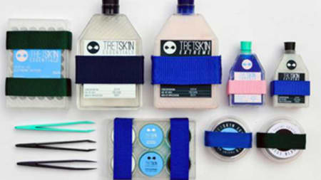 A flat lay of different pastel coloured bottles, tweezers and capsules.