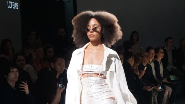 Model with afro in white taped clothing on the BA18 catwalk