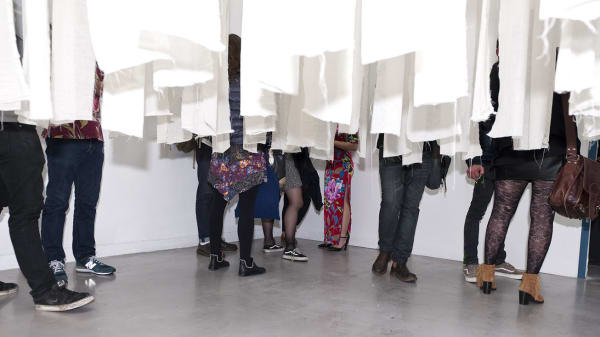People standing inside an installation of white strips of paper hanging from the ceiling