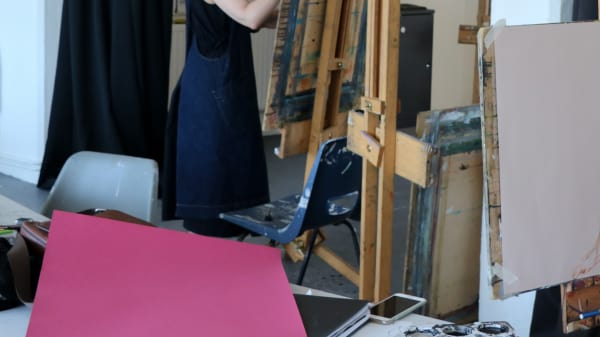 Student painting a figure