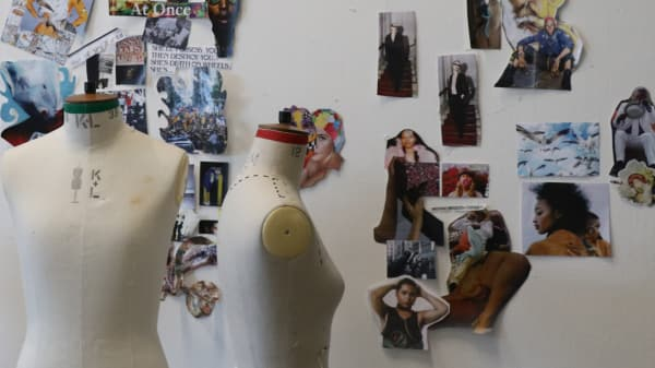 Mannequins next to student work pin to wall