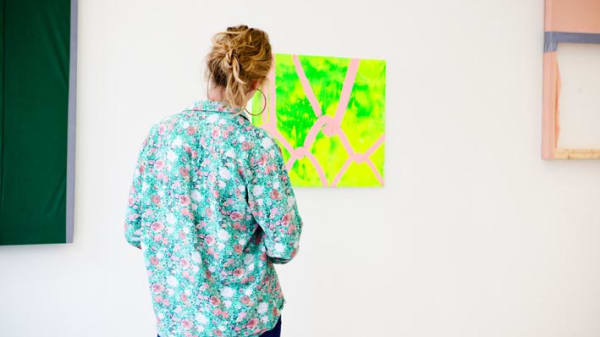 Girl in floral shirt looking at yellow picture on the wall