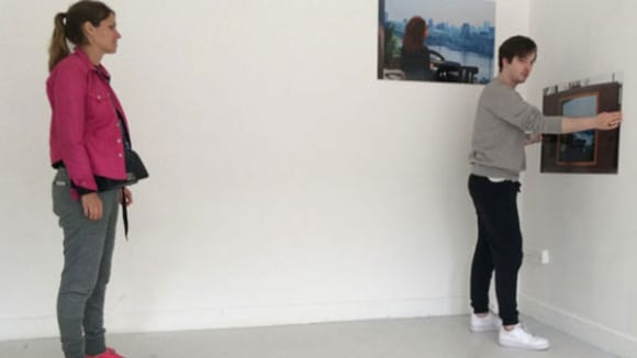 Photo of two people standing in a white room hanging pictures