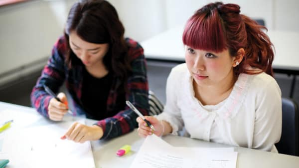 Photo of two female students sitting at a table writing