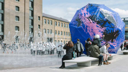 A large purple and blue multi-sided shape is placed in the middle of Granary Square, in front of Central Saint Martins