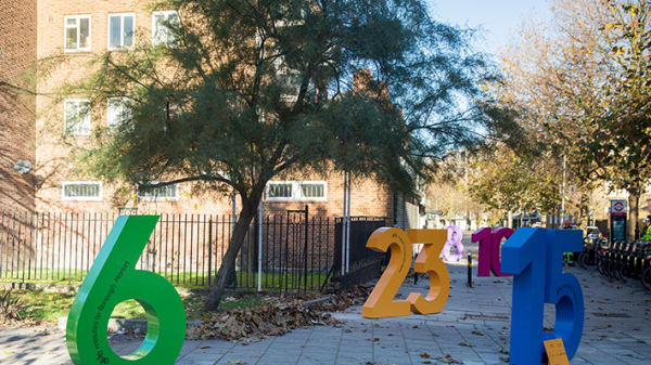 Several colourful and oversized numbers positioned near a hire bike stand.