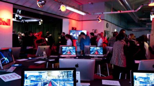 People at an event in a gallery featuring various computer screens