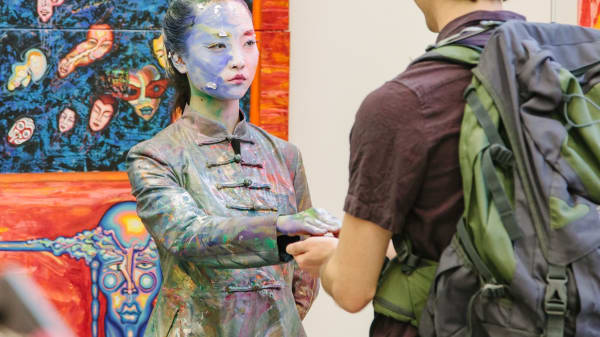 A performance artist covered in paint holding out a hand to a Degree Show guest