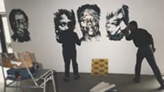 Photo of two people standing in front of a wall with paintings of faces on it