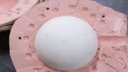 Close up image of a pink and wide oval 3D object