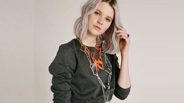 Photo of a woman wearing a grey jumper with a large orange necklace