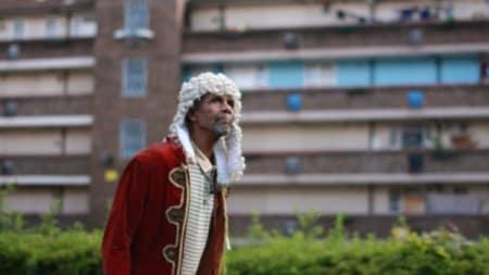 A man wearing a judges wig walking through an estate
