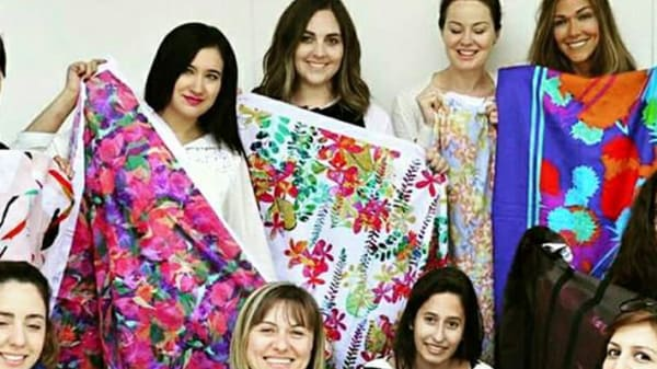 Six women holding up different pieces of patterned material